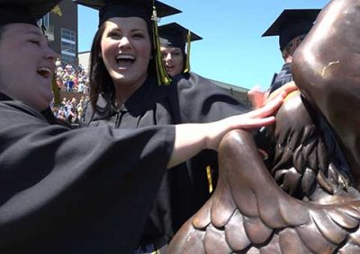 Graduates rub the Griffon's head
