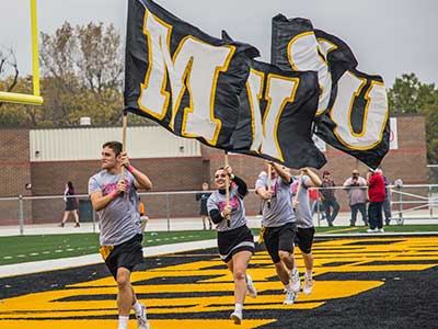 Cheerleaders carry in MWSU flags at a football game