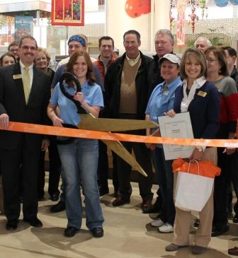 Owner of Auntie Anne's Pretzels cutting the ribbon at the grand opening of the store.