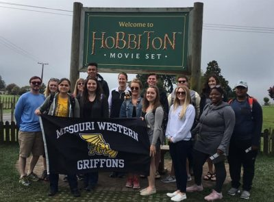 Students pose in front of sign that says Welcome to Hobbiton Movie Set, while holding a Missouri Western Griffons flag.