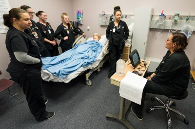Nursing students practice with a manikin
