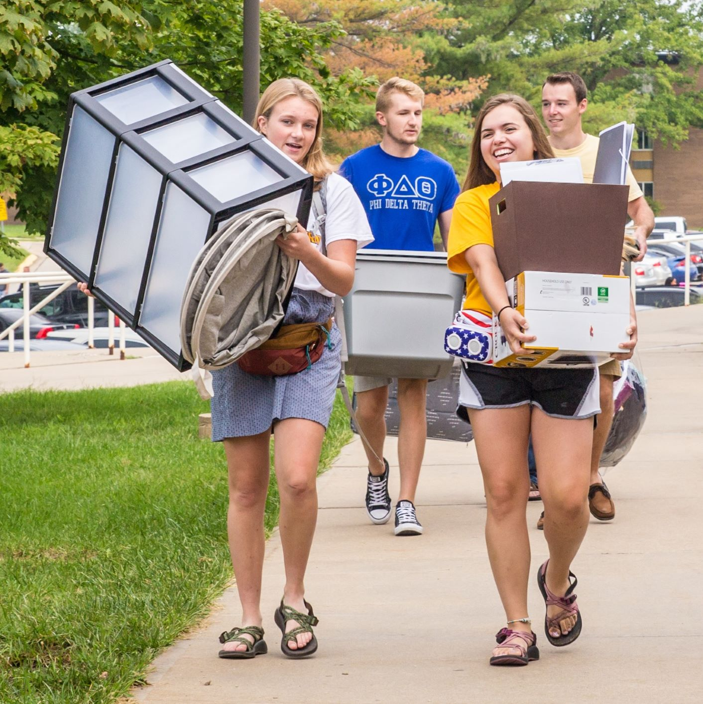 two students carry boxes and containers across campus