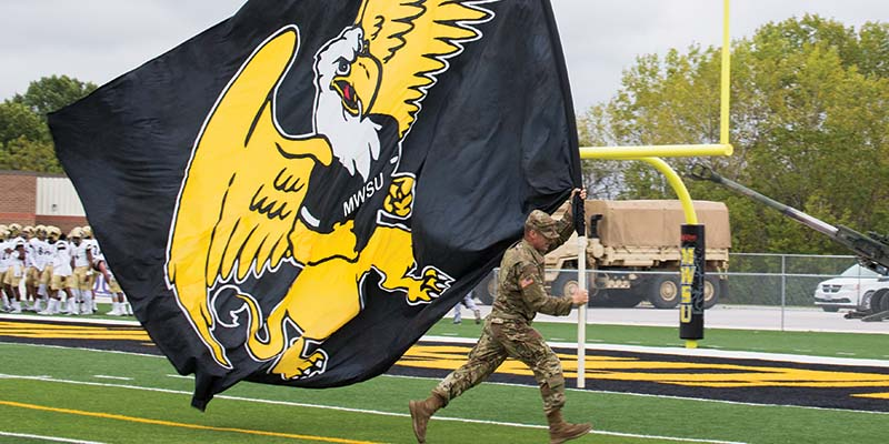 Military service member running with MWSU flag