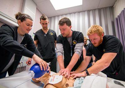 Nursing students using sim man