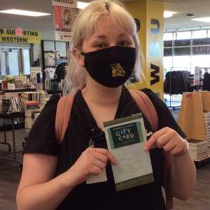 bailey daniels at student store holding a gift card