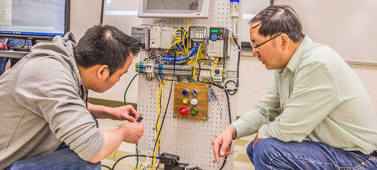Engineering student and professor work on a wiring project