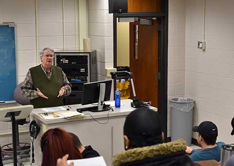Economics professor lectures in class