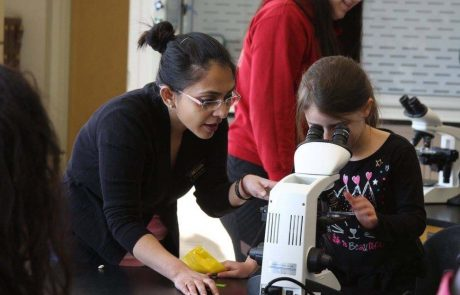 Dr. Tilottama Roy helping elementary student with a microscope