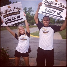 Students holding Griffon Edge Check-In signs