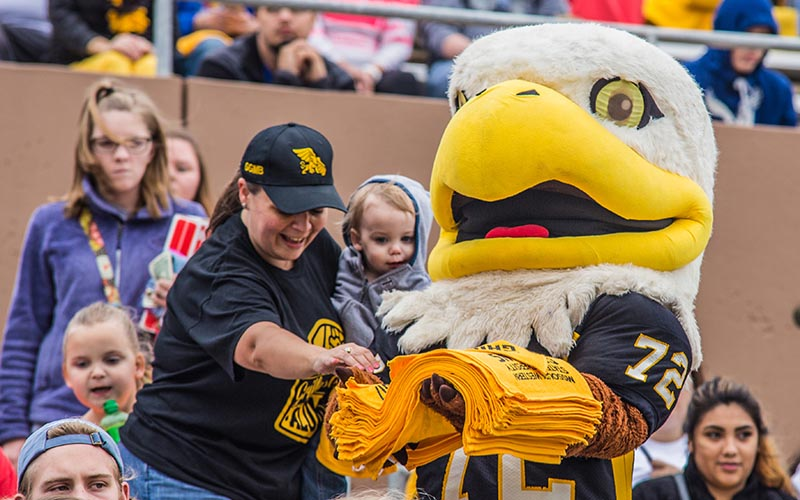Community members grab a rally towel from Max the griffon at homecoming