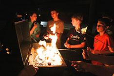Children gather around a camp fire