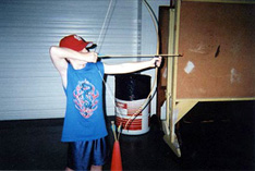Child shooting an arrow during archery lesson
