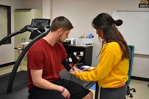 Students practice taking each others blood pressure