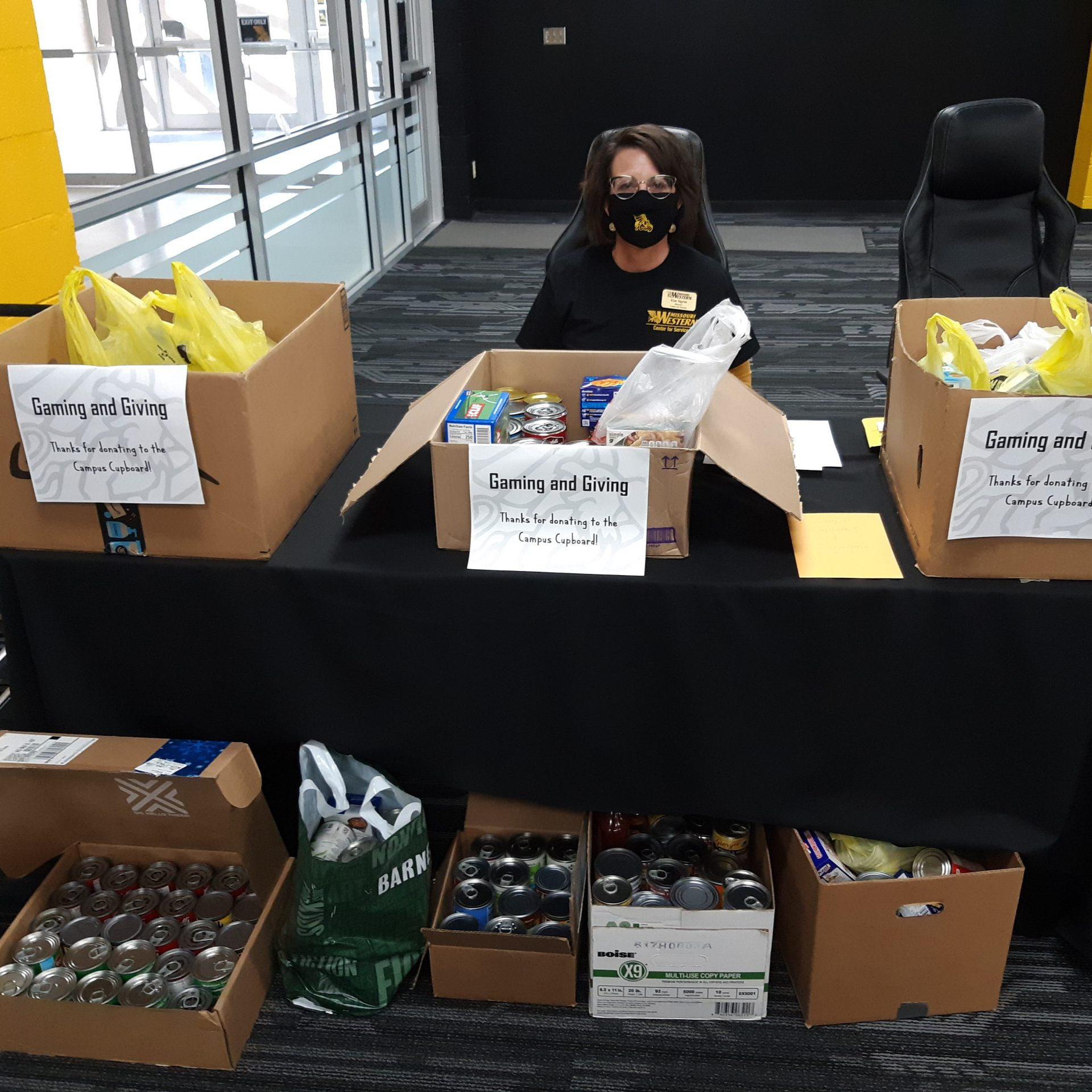 Kim Sigrist sits at a table behind several boxes of donated food.