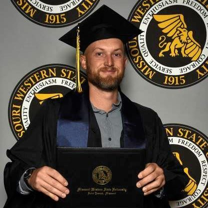 lian nevin posing in his cap and gown holding his diploma