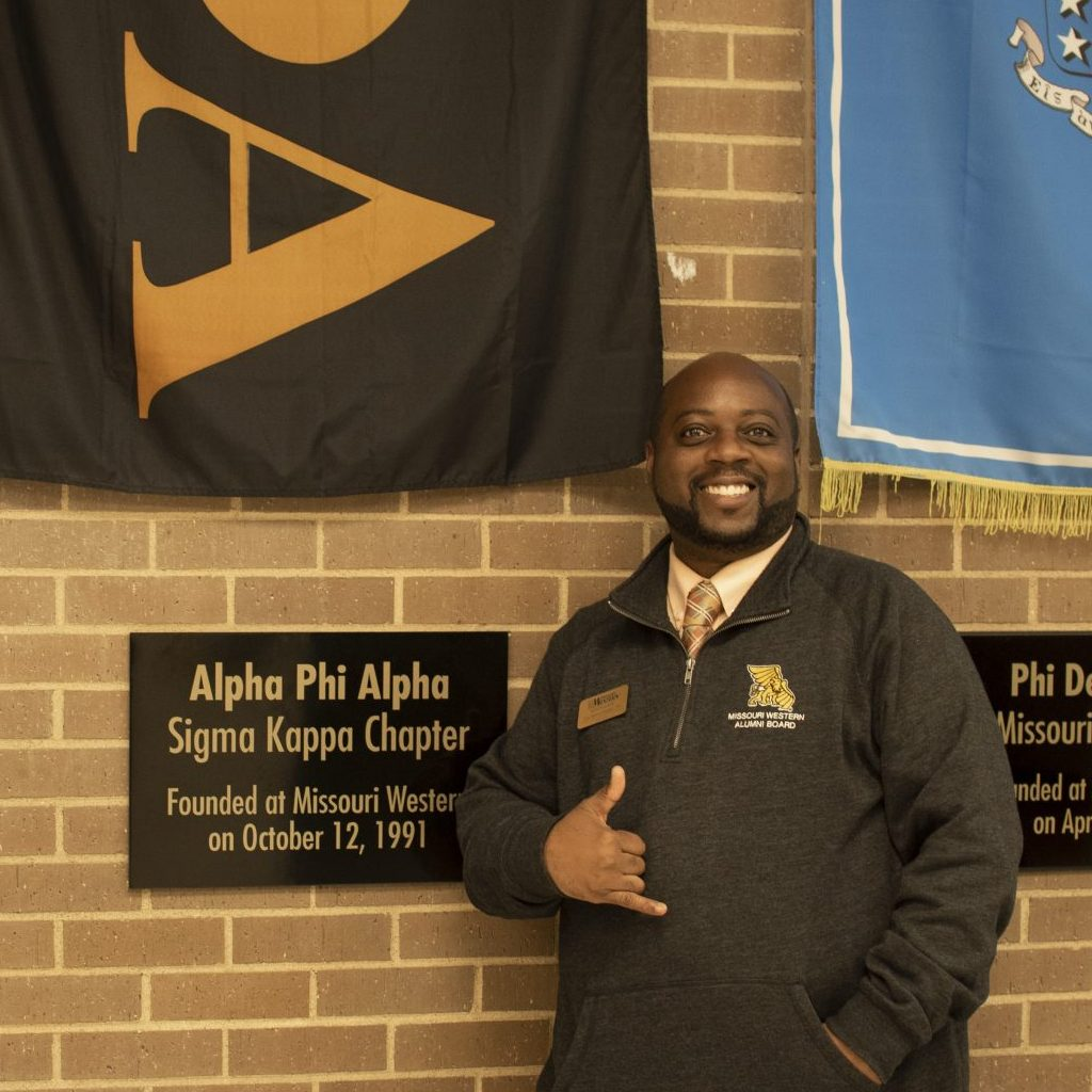 Lai-Monté Hunter posing in front of the Alpha Phi Alpha Sigma Kappa Chapter flag and plaque