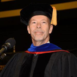 Dr. Doug Davenport standing at podium in regalia