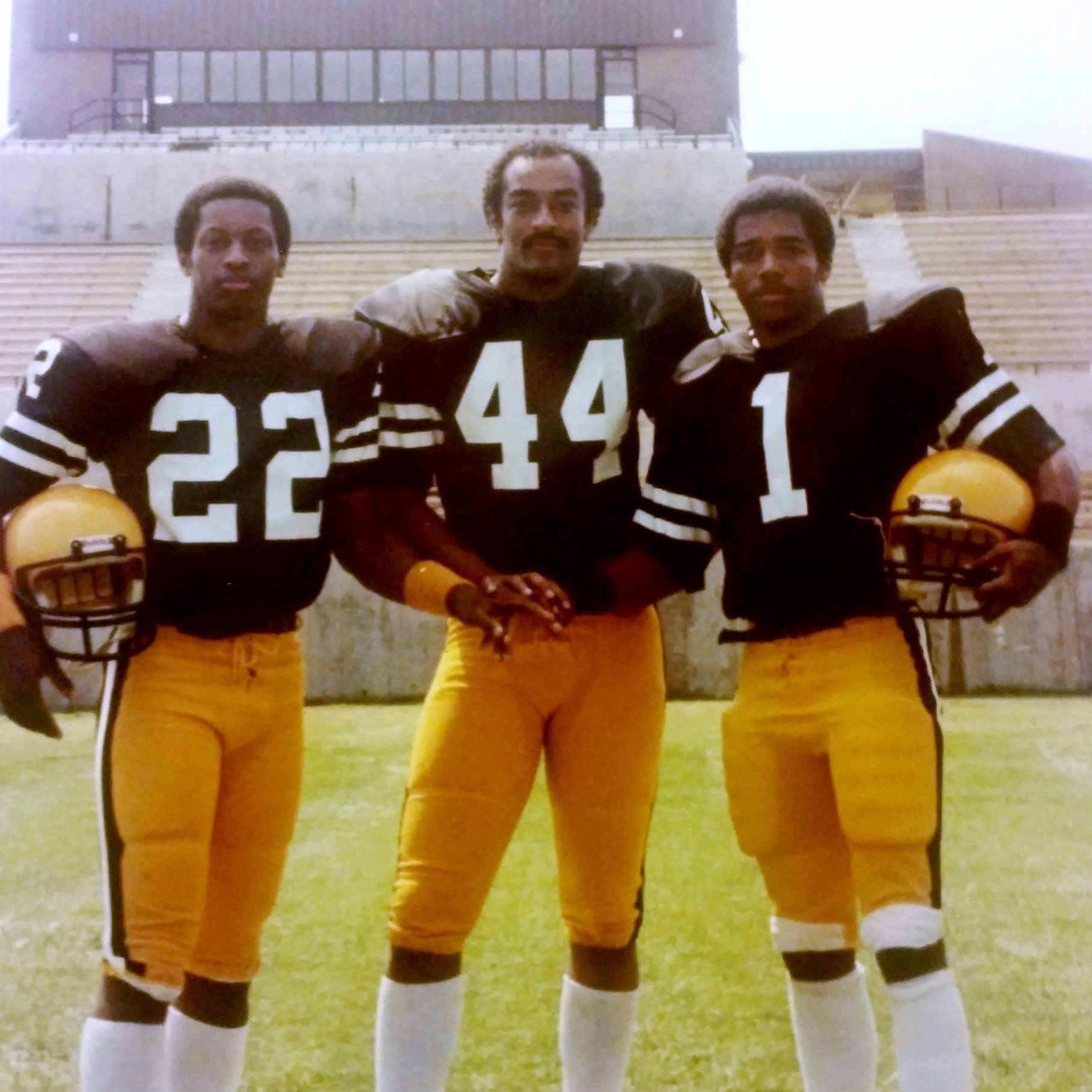 Tim Hoskins, Rodney Stephenson and Marc Lewis posing for photo in football uniforms, spratt stadium in background