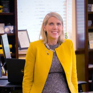 president kennedy leaning on her desk
