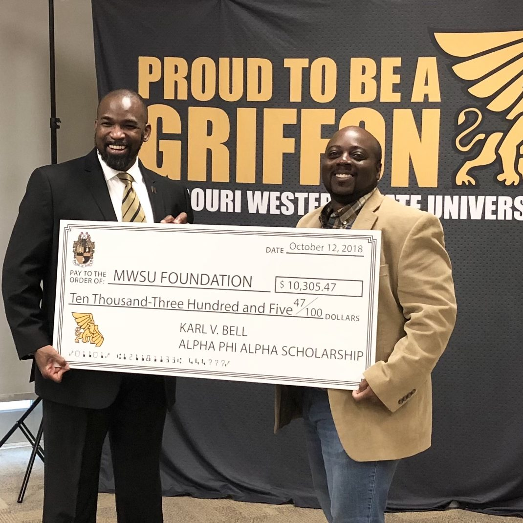 karl bell and Lai-Monté Hunter holding an oversized donation check