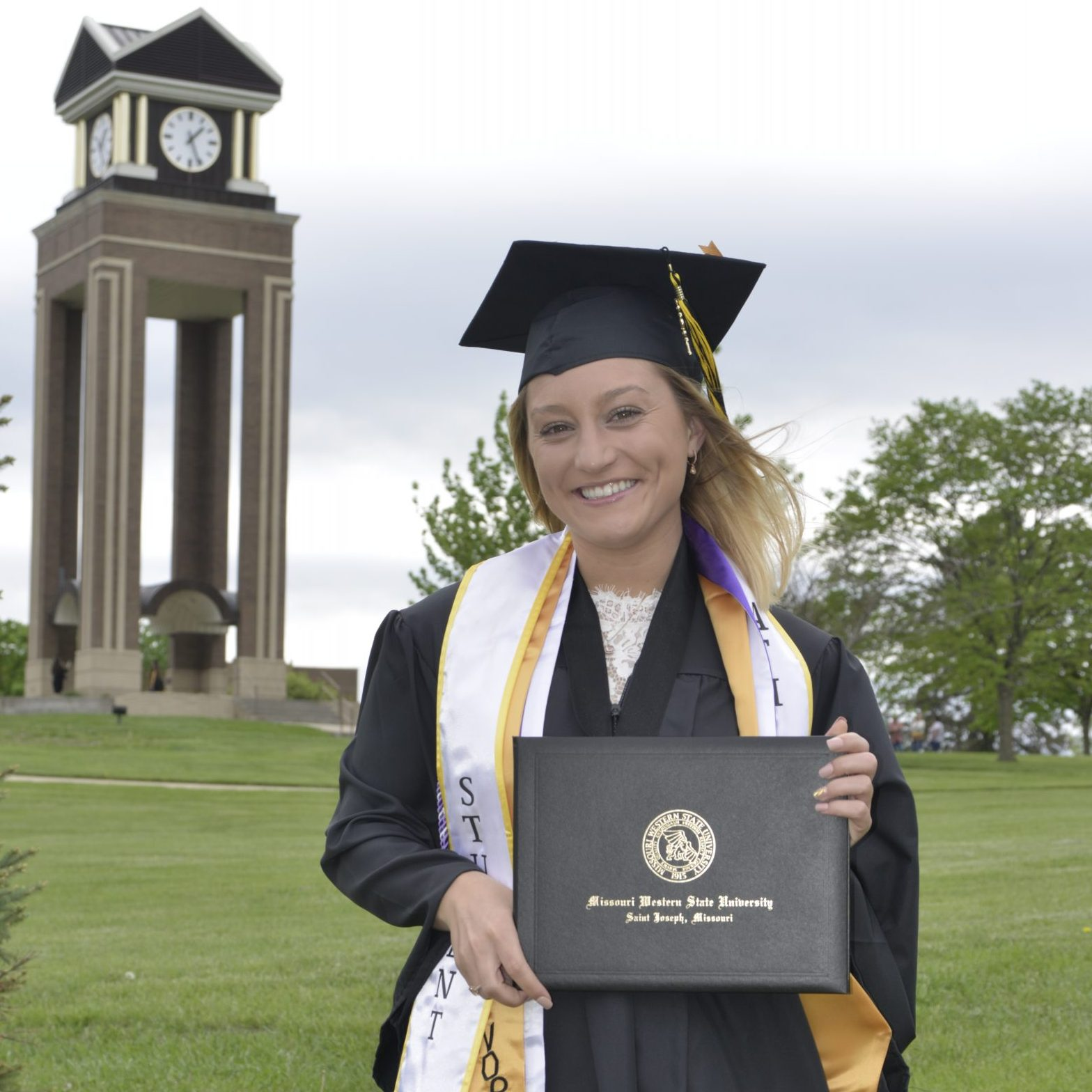 mackenzie oneill posing in front of the clocktower with her diploma