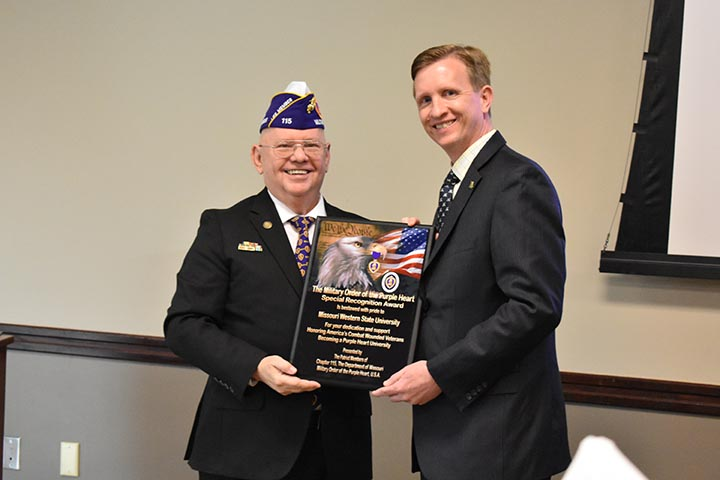 MWSU president Matt Wilson shows off the Purple Heart University designation plaque