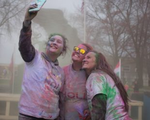 three Missouri Western students covered in colored powder take a selfie during Holi celebration