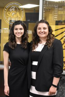 Andrea Hall and Michelle Scott stand in front of the SGA Office in Blum Union