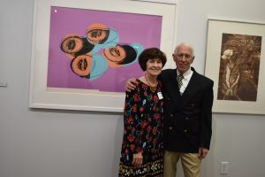 Edith and William Eickhorst stand in front of an Andy Warhol print