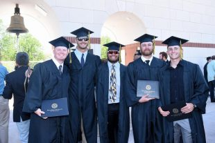 graduates smile after receiving diplomas