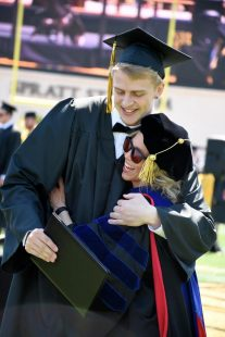 professor hugs a graduating student