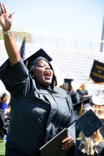 graduate celebrates after receiving her diploma