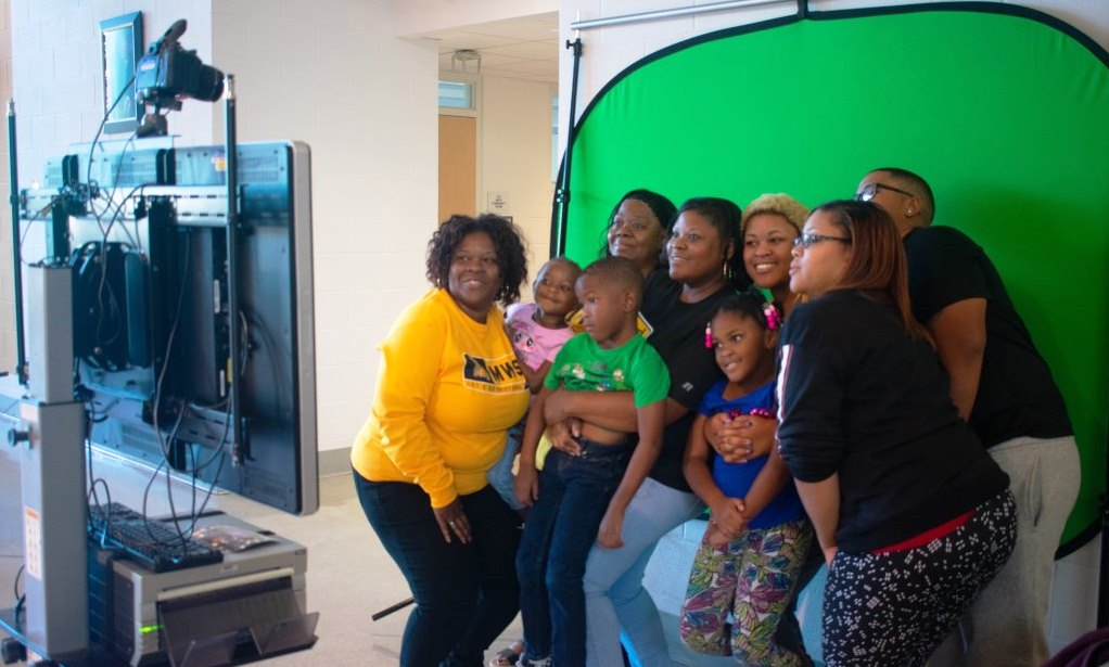 adults and children pose in a photo booth at Missouri Western's family weekend