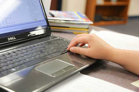 Students hand typing on a laptop