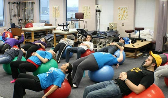 Students stretch on medicine ball