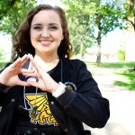 Kaley Dittemore shows Tri Sigma hand sign.